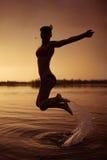 La ragazza salta in fiume al tramonto immagini stock