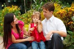 La ragazza salta le bolle di sapone in giardino con i genitori Fotografia Stock