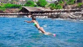 La ragazza salta nel mare blu stock footage