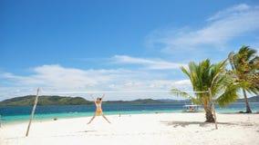 La ragazza salta nell'ambito della rete di pallavolo sulla spiaggia bianca fotografia stock libera da diritti