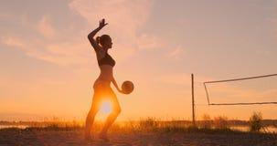 La ragazza salta la pallavolo sulla spiaggia, movimento lento di servire archivi video