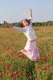 La ragazza salta sopra il campo del papavero Fotografia Stock