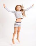 La ragazza salta su una priorità bassa bianca fotografia stock libera da diritti