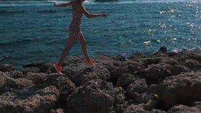 La ragazza salta sulle pietre al mare video d archivio
