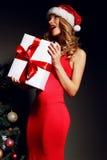 La ragazza in Santa-cappello che giudica regalo-scatole si avvicina all'albero di Natale Immagini Stock Libere da Diritti