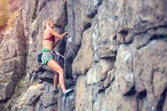 La ragazza scala la roccia Immagine Stock