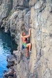 La ragazza scala la roccia Fotografie Stock