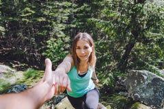 La ragazza scala su roccia, partner estrae la mano per assistenza fotografie stock libere da diritti