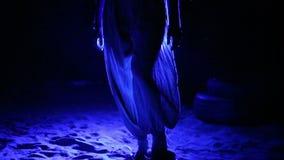La ragazza scalza in ampi pantaloni cammina sulla sabbia alla luce dei riflettori colorati archivi video