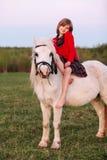 La ragazza scalza della piccola giovane signora che si siede su un cavallino e lancia immagine stock libera da diritti