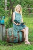 La ragazza scalza dello studente in giardino è libro di lettura con la copertura blu Immagine Stock Libera da Diritti