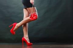La ragazza in scarpe appuntite rosse del breve vestito nero tiene la borsa immagine stock libera da diritti