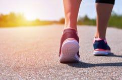La ragazza in scarpe da corsa funziona lungo la strada, solo le sue gambe sono visibili, gambe e le scarpe da tennis, luce solare Immagine Stock