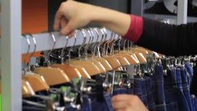 La ragazza sceglie i jeans nel deposito stock footage