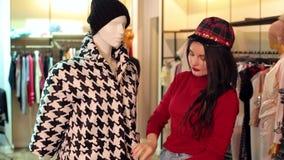 La ragazza sceglie i vestiti nel deposito, lei sceglie un cappotto in bianco e nero di autunno stock footage