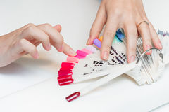 La ragazza sceglie il colore di polacco per il manicure Fotografia Stock Libera da Diritti