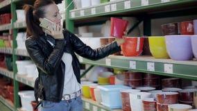 La ragazza sceglie un vaso di fiore nel supermercato Cliente della donna nel negozio di fiore archivi video
