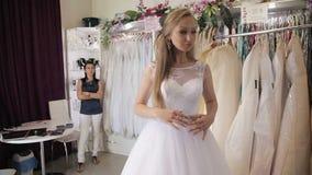 326639b12b4a9 La ragazza sceglie un vestito da sposa in un salone di nozze archivi video