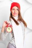 La ragazza in sciarpa e cappello mostra il tempo Fotografie Stock