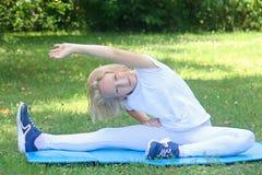 La ragazza scolare del bambino in vestiti leggeri prende l'esercizio di sport su una stuoia nel parco All'aperto allenamento Immagini Stock Libere da Diritti