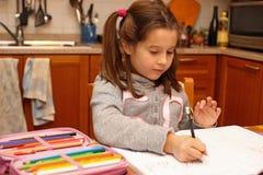 La ragazza scrive con la matita il suo compito nella cucina Immagini Stock Libere da Diritti