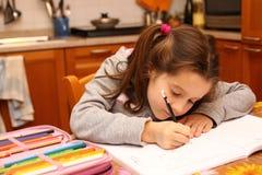 La ragazza scrive con la matita sul libro di scuola Fotografie Stock