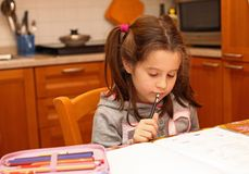 La ragazza scrive con la matita sul libro di scuola Fotografia Stock Libera da Diritti