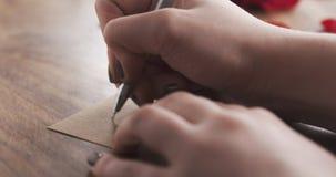 La ragazza scrive l'8 marzo su una carta di carta su vecchio fondo di legno Fotografia Stock