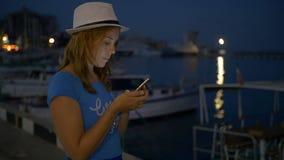 La ragazza scrive nel messaggero sul telefono cellulare sul cielo notturno del fondo video d archivio