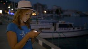 La ragazza scrive nel messaggero sul telefono cellulare sul cielo notturno del fondo archivi video