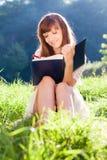 La ragazza scrive qualcosa in un libro che si siede all'erba Immagini Stock