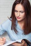 La ragazza scrive in un giornale che sta tenendo in sua mano Fotografia Stock