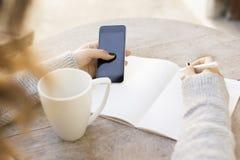 La ragazza scrive in un taccuino, con il telefono cellulare e la tazza di caffè Fotografie Stock