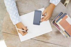 La ragazza scrive in un taccuino, con il telefono cellulare ed i libri Immagini Stock