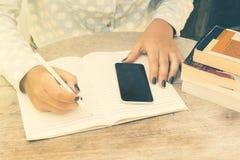 La ragazza scrive in un taccuino, con il telefono cellulare ed i libri Fotografie Stock Libere da Diritti