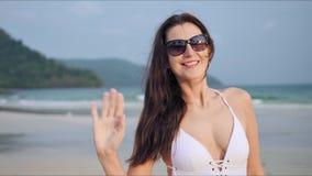 La ragazza seducente con capelli lunghi si è vestita in un costume da bagno bianco che posa sulla spiaggia tropicale archivi video