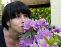 La ragazza sente l'odore dei fiori viola Fotografia Stock