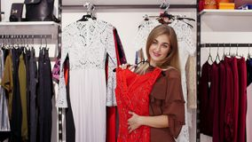 La ragazza sexy, donna bionda alta e bella sceglie i vestiti nel deposito, pieno d'ammirazione davanti ad uno specchio, sorrisi stock footage