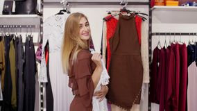 La ragazza sexy, donna bionda alta e bella sceglie i vestiti nel deposito, pieno d'ammirazione davanti ad uno specchio, sorrisi video d archivio