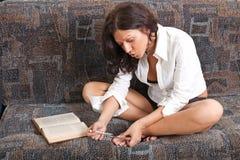 La ragazza sexy legge un libro Immagine Stock Libera da Diritti