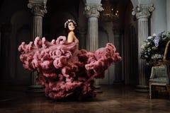 La ragazza sexy lussuosa in un vestito nuvoloso da sera balla e si gira ad una palla fotografie stock