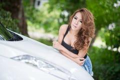 La ragazza sexy in maglia nera sta posando sull'automobile del cappuccio Immagini Stock
