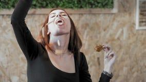 La ragazza sexy mangia gli alimenti a rapida preparazione Fritture versate nella vostra bocca Il concetto della società di obesit archivi video