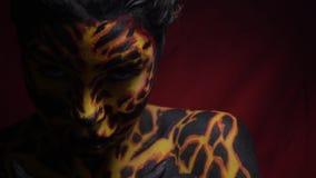 La ragazza sexy nella vernice di carrozzeria con un'immagine della lava si trasforma in acutamente la macchina fotografica e gli  stock footage