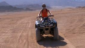 La ragazza sexy su una bici del quadrato guida attraverso il deserto dell'Egitto su fondo delle montagne video d archivio