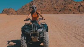 La ragazza sexy su una bici del quadrato guida attraverso il deserto dell'Egitto su fondo delle montagne archivi video