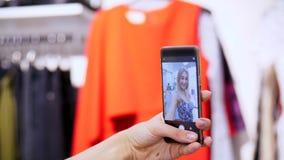La ragazza sexy, una bella donna bionda fa il selfie in una nuova attrezzatura, sorridente, in un deposito, un boutique dei vesti video d archivio