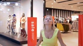 La ragazza shopaholic sorridente ottiene il piacere dai nuovi acquisti agli sconti stagionali nel deposito di modo in centro comm archivi video