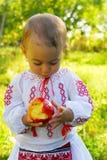 La ragazza si è vestita in costume tradizionale e nel cibo della mela immagini stock