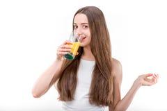La ragazza si è vestita in un succo d'arancia bevente della camicia bianca Fotografia Stock